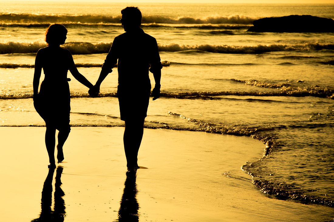 holding hands portrait in the evening sun on a Cornwall beach