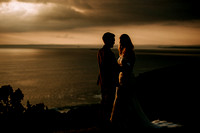 Gorgeous back lit wedding portrait of newlyweds in a stunning Cornish cliff top setting