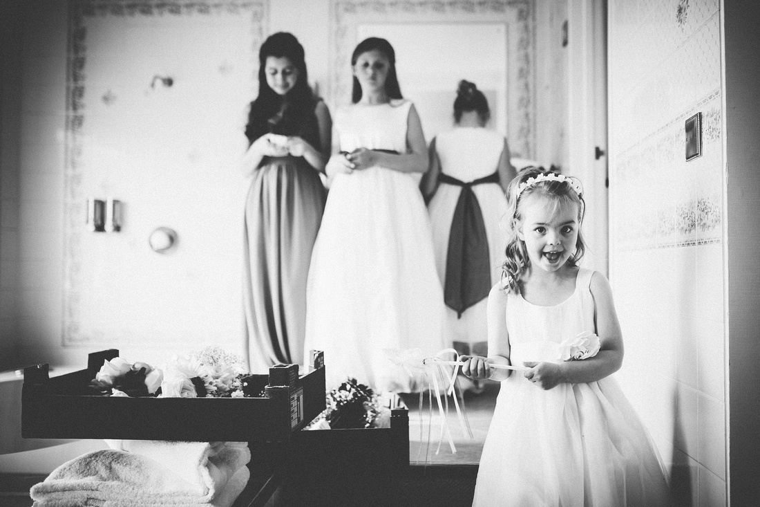 Delighted flower girl joining in the wedding preparations at this Merchants Manor wedding venue